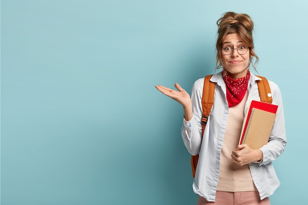 Doubtful unaware schoolgirl raises palm, holds spiral notepad, carries rucksack, gestures over blue blank space