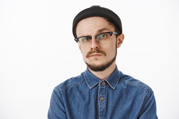 Dubbioso e incerto imprenditore prepotente dall'aspetto serio in camicia nera e occhiali che alza un sopracciglio in esitazione e incredulità in piedi non emotivo e sospettoso