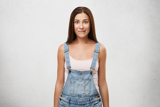 Doubtful uncertain young brunette woman in denim jumpsuit biting her lower lip, looking frustrated, her brown eyes full of doubt and hesitation. human facial expressions and emotions