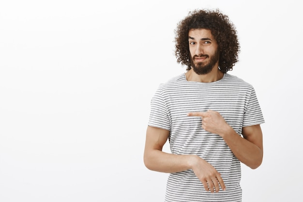 Doubtful unimpressed handsome eastern guy with beard and curly hairstyle in striped t-shirt, pointing left and lifting eyebrow with suspicious disbelieving expression