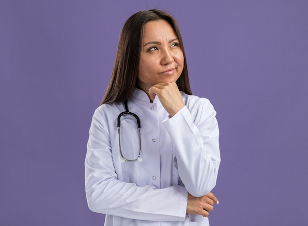 Doubtful young asian female doctor wearing medical robe and stethoscope keeping hand on chin looking up isolated on purple wall with copy space