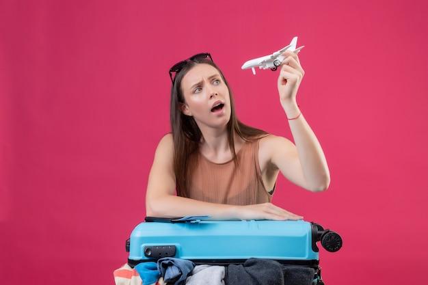 ピンクの壁に不確かなおもちゃの飛行機を保持している服の旅行スーツケースでいっぱい疑わしい若い美しい女性