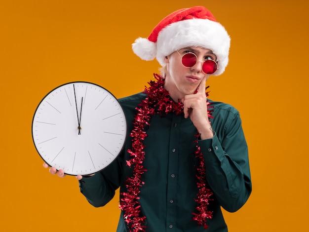 오렌지 배경에 고립 된 턱에 손을 유지하는 측면을보고 시계를 들고 목 주위에 반짝이 갈 랜드와 산타 모자와 안경을 쓰고 의심스러운 젊은 금발의 남자