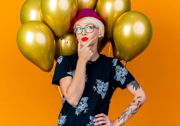 Dubbioso giovane bionda party girl indossando party hat e occhiali in piedi di fronte a palloncini mantenendo la mano sulla vita toccando il mento guardando lato isolato su sfondo arancione