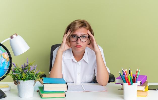 Dubbiosa giovane studentessa bionda con gli occhiali seduto alla scrivania con gli strumenti della scuola tenendo le mani sulla testa guardando la telecamera isolata sul muro verde oliva