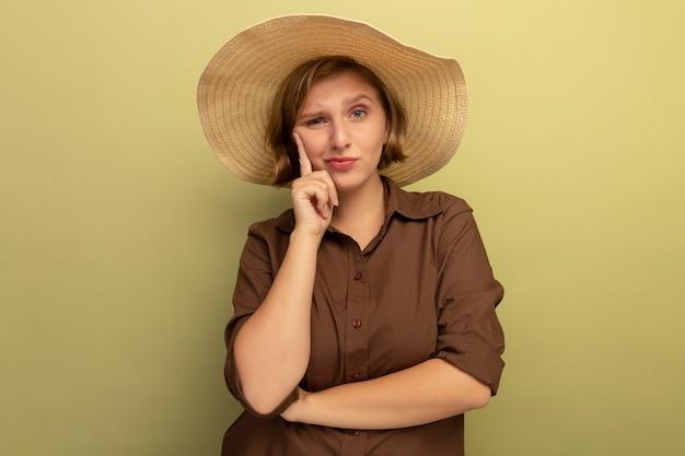 해변 모자를 쓴 의심스러운 젊은 금발 여성이 복사 공간이 있는 올리브 녹색 벽에 고립된 정면을 바라보는 얼굴에 손을 대고 있습니다.
