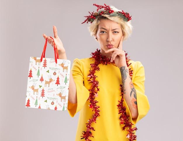 クリスマスの頭の花輪と首の周りに見掛け倒しの花輪を身に着けている疑わしい若いブロンドの女性は、白い壁で隔離されたあごに手を保ちながらクリスマスギフトバッグを保持しています