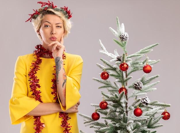 クリスマスの頭の花輪と首の周りに見掛け倒しの花輪を身に着けている疑わしい若いブロンドの女性は、白い背景で隔離のあごに手を置いてカメラを見ている装飾されたクリスマスツリーの近くに立っています
