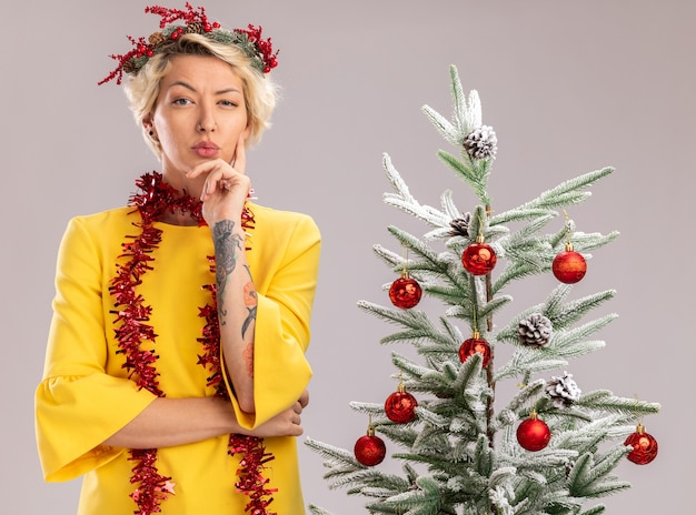 Doubtful young blonde woman wearing christmas head wreath and tinsel garland around neck standing near decorated christmas tree looking at camera keeping hand on chin isolated on white background