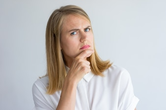 Doubtful young Caucasian businesswoman wearing white shirt analyzing some idea