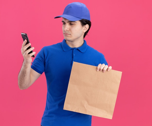 Doubtful young caucasian delivery man in blue uniform and cap holding paper package and mobile phone looking at phone