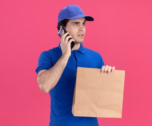 Dubbioso giovane fattorino caucasico in uniforme blu e cappuccio che tiene un pacchetto di carta parlando al telefono guardando a lato