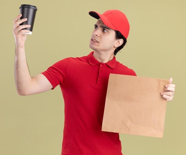 Dubbioso giovane fattorino caucasico in uniforme rossa e cappuccio che tiene in mano un pacchetto di carta e una tazza di caffè in plastica che si alza e guarda la tazza