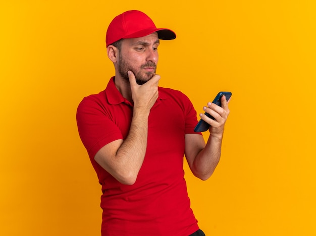 Doubtful young caucasian delivery man in red uniform and cap keeping hand on chin holding and looking at mobile phone isolated on orange wall
