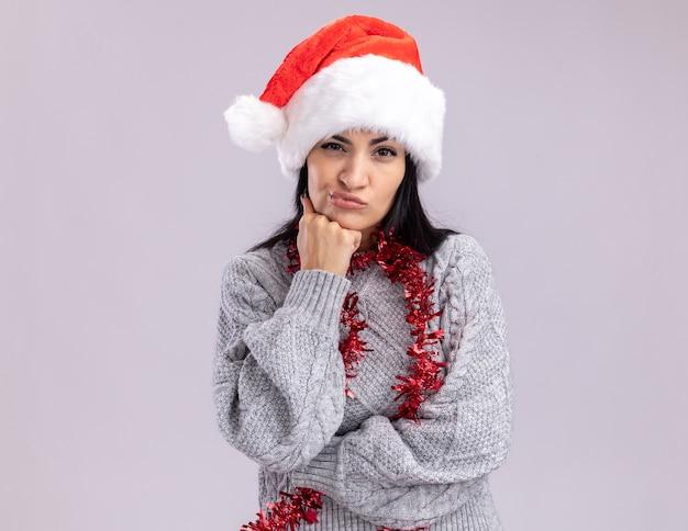 Сомнительная молодая кавказская девушка в новогодней шапке и мишурной гирлянде на шее, глядя в камеру, держа руку под подбородком на белом фоне