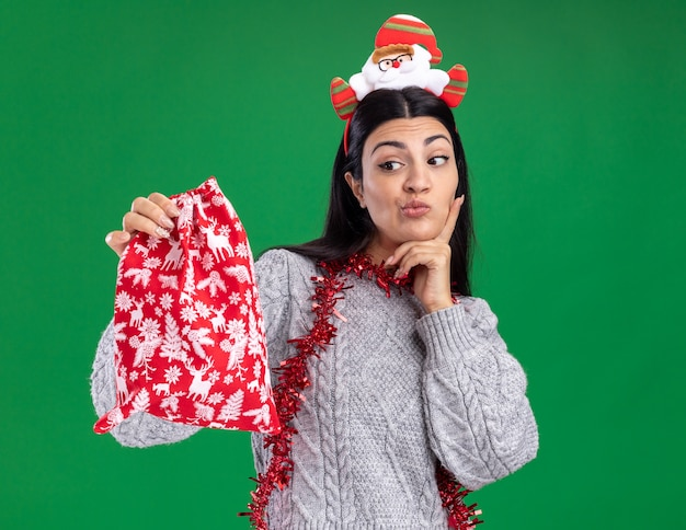 疑わしい若い白人の女の子は、サンタクロースのヘッドバンドと見掛け倒しのガーランドを首の周りに身に着けて、緑の壁で隔離されたあごに手を置いてクリスマスプレゼントの袋を見て見ています
