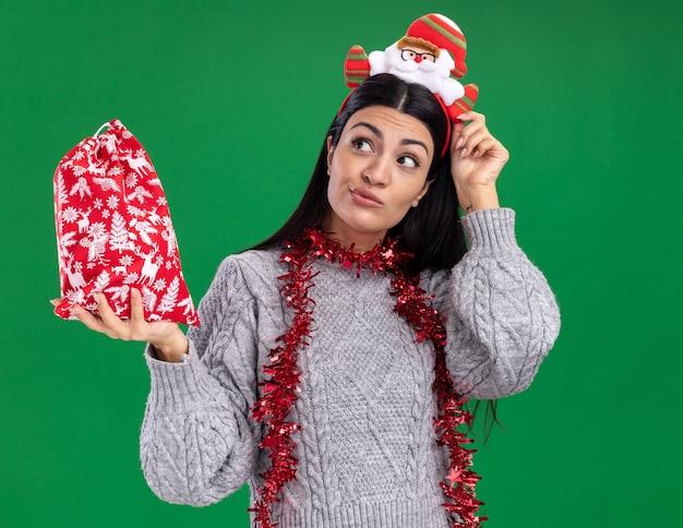 Сомневающаяся молодая кавказская девушка в головной повязке санта-клауса и гирлянде из мишуры на шее держит мешок рождественского подарка, трогая повязку, глядя в сторону, изолированную на зеленом фоне