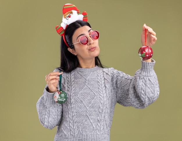 Dubbioso giovane ragazza caucasica che indossa la fascia di babbo natale con gli occhiali tenendo le bagattelle di natale guardando uno di loro isolato su sfondo verde oliva