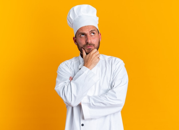 Doubtful young caucasian male cook in chef uniform and cap keeping hand on chin looking up isolated on orange wall with copy space