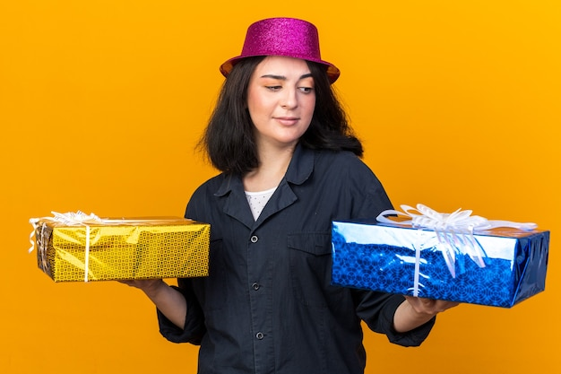 Doubtful young caucasian party girl wearing party hat holding gift packages looking at one of them isolated on orange wall
