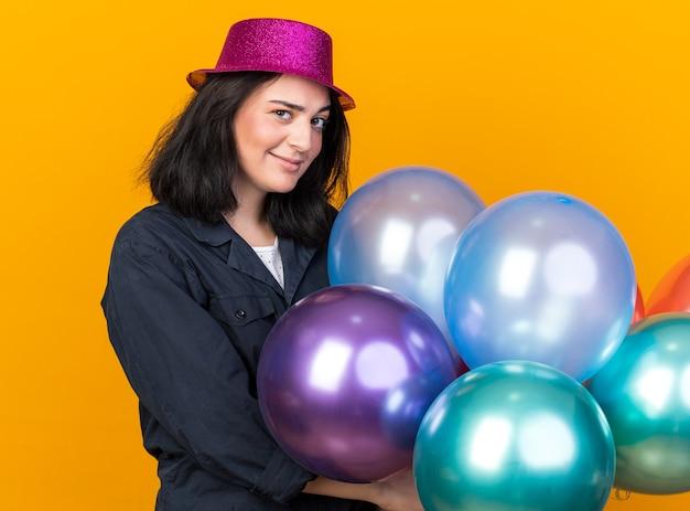 オレンジ色の壁に隔離された正面を見て風船を保持している縦断ビューで立っているパーティー帽子をかぶっている疑わしい若い白人パーティーの女性