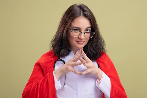 医者の制服と聴診器を身に着けている赤いマントの疑わしい若い白人のスーパーヒーローの女の子は、手を一緒に保つ眼鏡をかけています