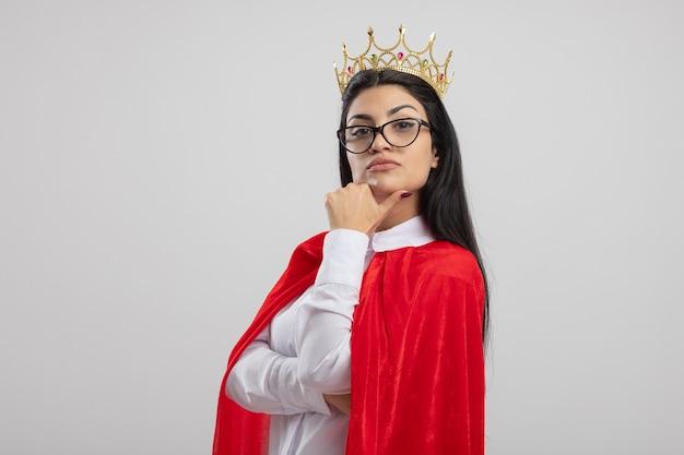 Сомнительная молодая кавказская девушка супергероя в очках и короне, стоящая в профиле, глядя в камеру, трогательно подбородок, изолированные на белом фоне с копией пространства