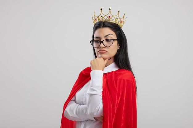 眼鏡と王冠を身に着けている疑わしい若い白人のスーパーヒーローの女の子は、コピースペースで白い背景に分離された見下ろしているあごに触れているカメラを見て縦断ビューで立っています