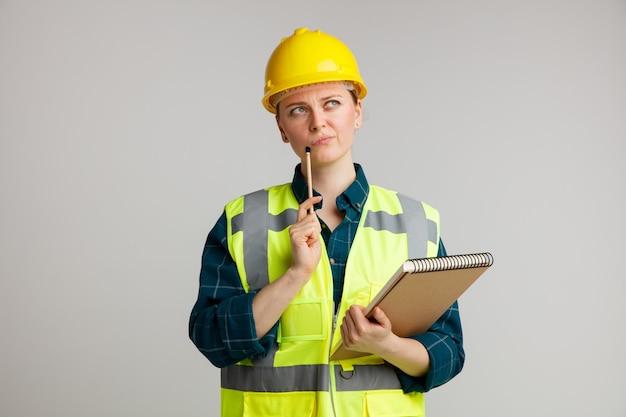 Сомневающаяся молодая женщина-строитель в защитном шлеме и жилете держит блокнот, касаясь подбородка карандашом, глядя вверх
