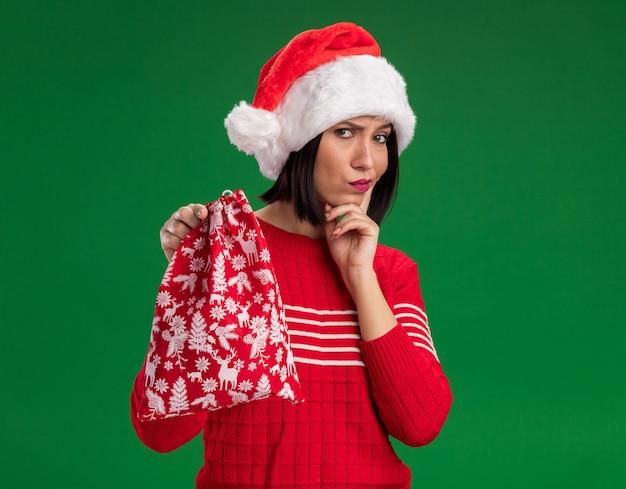 Сомнительная молодая девушка в шляпе санта-клауса, держащая рождественский подарочный мешок, держа руку на подбородке, изолированную на зеленой стене с копией пространства