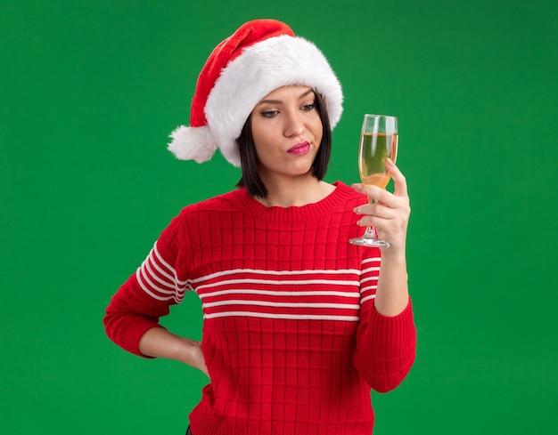 Ragazza dubbiosa che porta la tenuta del cappello della santa e che esamina il bicchiere di champagne che tiene la mano sulla vita isolata sulla parete verde