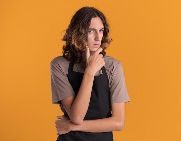 Dubbioso giovane barbiere bello che indossa l'uniforme tenendo la mano sul mento guardando la parte anteriore isolata sulla parete arancione con spazio di copia