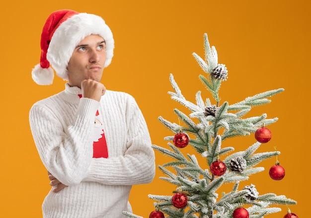 クリスマスの帽子とサンタクロースのネクタイを身に着けている疑わしい若いハンサムな男は、オレンジ色の背景に孤立して見上げる装飾されたクリスマスツリーの近くに閉じた姿勢で立っています
