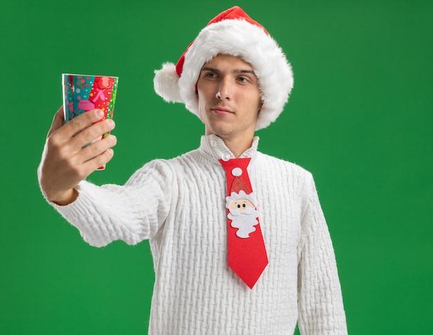 クリスマスの帽子とサンタクロースのネクタイを身に着けている疑わしい若いハンサムな男は、緑の背景に分離されたそれを見てカメラに向かってプラスチック製のクリスマスカップを伸ばしています
