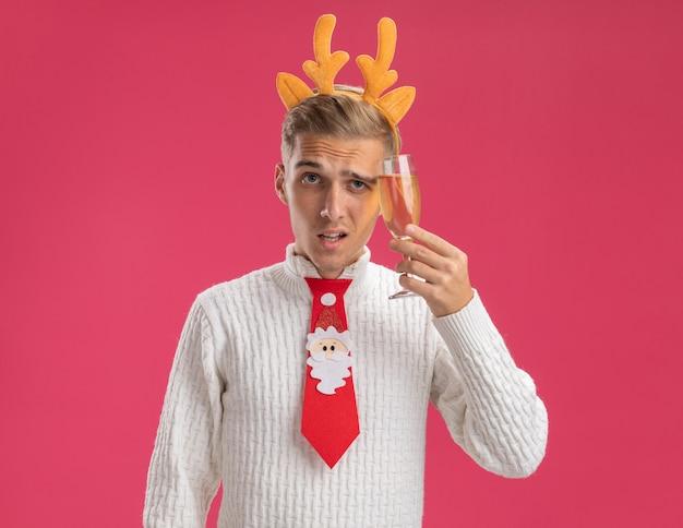순록 뿔 머리띠와 산타 클로스 넥타이를 입고 의심스러운 젊은 잘 생긴 남자가 분홍색 배경에 고립 된 카메라를보고 샴페인을 만지고 머리를 만지고 있습니다.
