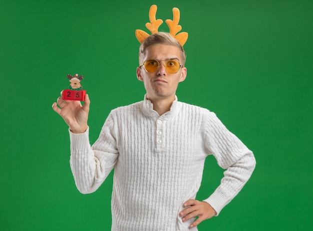 緑の背景に分離されたカメラを見て腰に手を保つトナカイの角のおもちゃを保持しているメガネとトナカイの角のヘッドバンドを身に着けている疑わしい若いハンサムな男