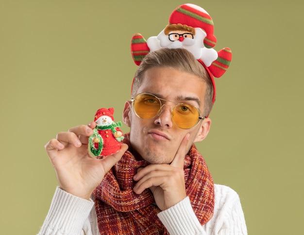 サンタクロースのヘッドバンドとスカーフを身に着けている疑わしい若いハンサムな男は、オリーブグリーンの背景で隔離の顔に指を保つ雪だるまのクリスマス飾りを保持しているカメラを見て