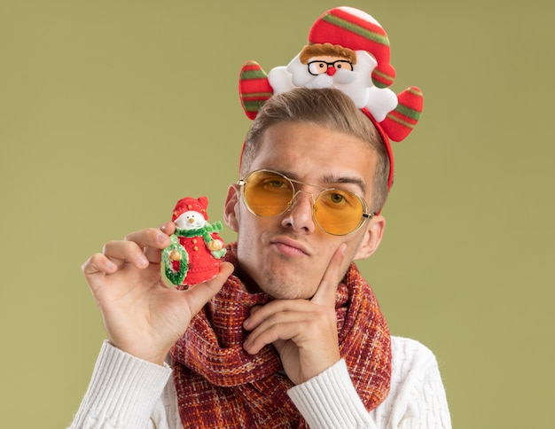 Dubbioso giovane bel ragazzo che indossa la fascia di babbo natale e sciarpa guardando la telecamera tenendo pupazzo di neve ornamento di natale mantenendo il dito sul viso isolato su sfondo verde oliva