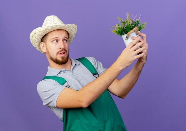 Dubbioso giovane giardiniere slavo bello in uniforme e cappello tenendo e guardando il vaso di fiori isolato sulla parete viola