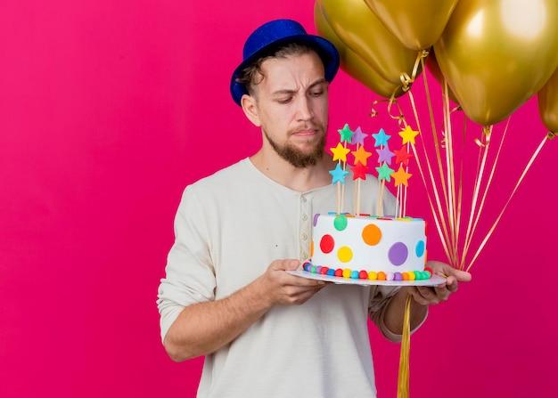 コピースペースでピンクの壁に分離されたケーキを見て星と風船とバースデーケーキを保持しているパーティーハットを身に着けている疑わしい若いハンサムなスラブパーティー男