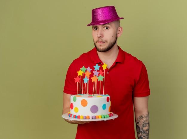 복사 공간 올리브 녹색 배경에 고립 된 카메라를보고 생일 케이크를 들고 파티 모자를 쓰고 의심스러운 젊은 잘 생긴 슬라브 파티 남자