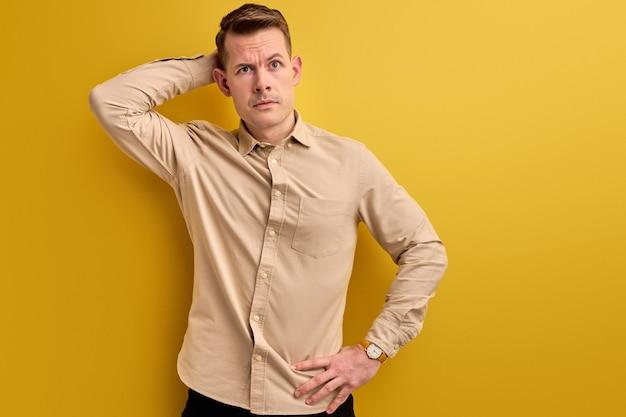 疑わしい青年は考えて立ち、質問を考えて頭の後ろを引っ掻き、物思いにふける表現。孤立した黄色のスタジオの壁