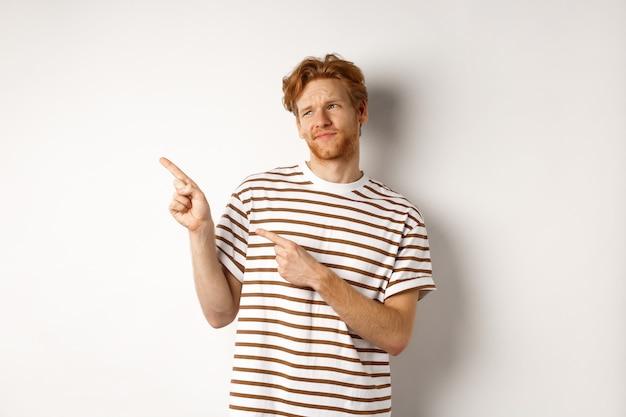 毛と赤い髪を見て、指を平均的なものに向け、プロモーション、白い背景に懐疑的な見つめている疑わしい若い男。