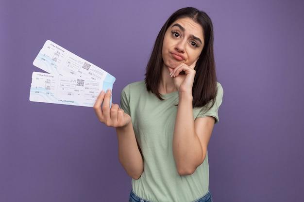 Dubbiosa giovane bella ragazza caucasica che tiene i biglietti dell'aereo tenendo la mano sul mento isolato sulla parete viola con spazio di copia