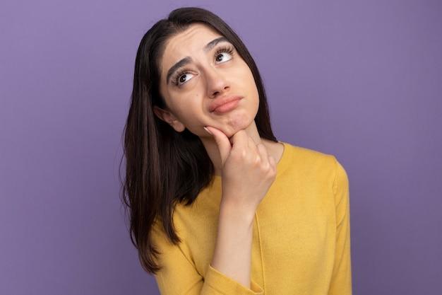 Dubbiosa giovane bella ragazza caucasica che tiene la mano sul mento guardando in alto isolato sul muro viola con spazio di copia