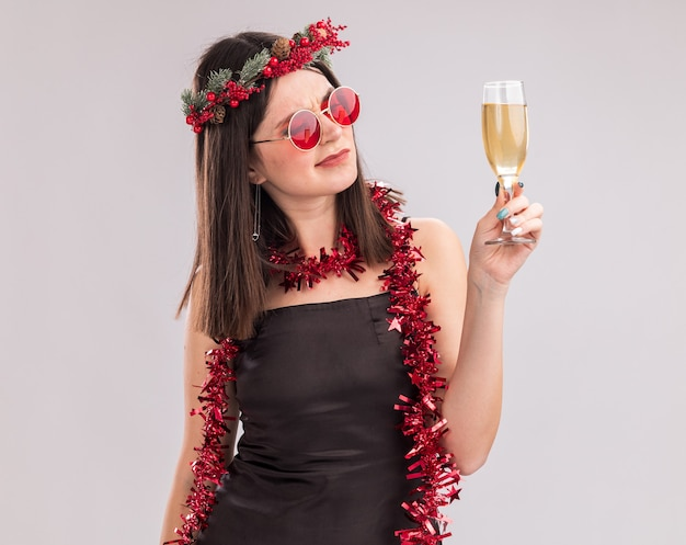 Doubtful young pretty caucasian girl wearing christmas head wreath and tinsel garland around neck with glasses holding and looking at glass of champagne isolated on white background