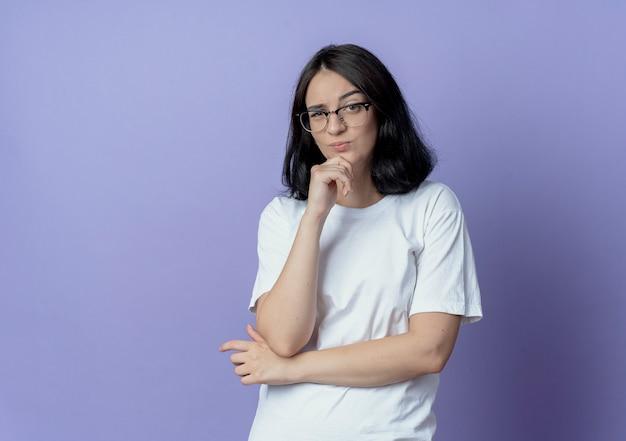 閉じた姿勢で立って、コピースペースと紫色の背景で隔離のあごに手を置いて眼鏡をかけている疑わしい若いかなり白人の女の子