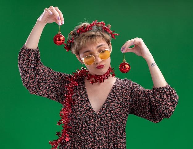 녹색 배경에 고립 된 그들 중 하나를 찾고 크리스마스 싸구려를 들고 안경 목에 크리스마스 머리 화 환과 반짝이 갈 랜드를 입고 의심스러운 젊은 예쁜 여자