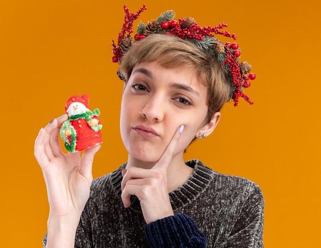 オレンジ色の背景で隔離のカメラを見て顔に触れる小さなクリスマス雪だるま像を保持しているクリスマスの頭の花輪を身に着けている疑わしい若いかわいい女の子