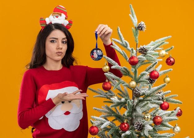 산타 클로스 머리띠와 스웨터를 입고 의심스러운 젊은 예쁜 여자